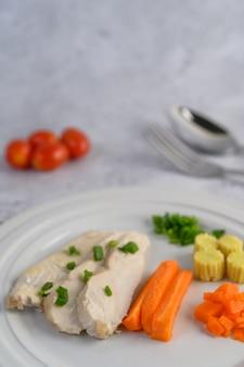 Peito de frango cozido no vapor em um prato branco com cebolinha, milho para bebê e cenoura picada.