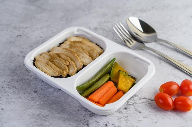 Peito de frango cozido no vapor em uma caixa de plástico com abóbora, cenoura, feijão e tomate.