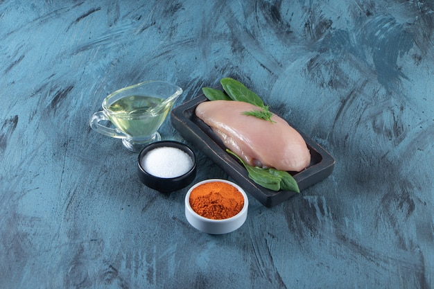 Peito de frango cru e espinafre em um prato de madeira ao lado de tigelas de especiarias, sal e óleo, na superfície azul.