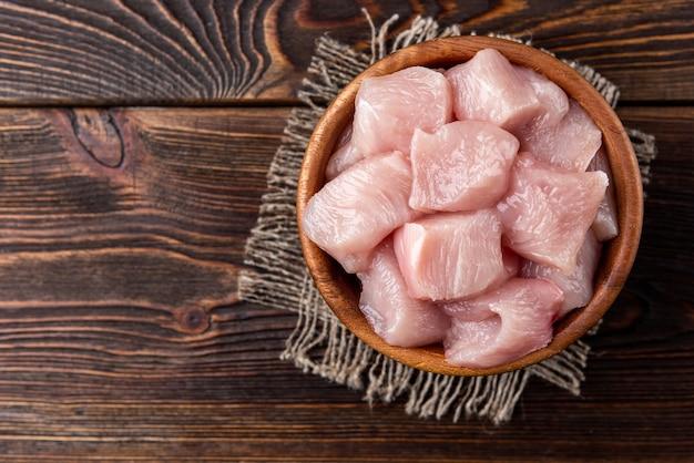 Peito de frango cru em cubos ou filetes no fundo escuro de madeira.