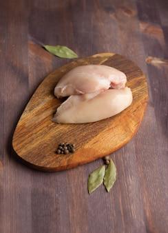 Peito de frango cru em uma placa apimentada, carne crua, fonte de proteína