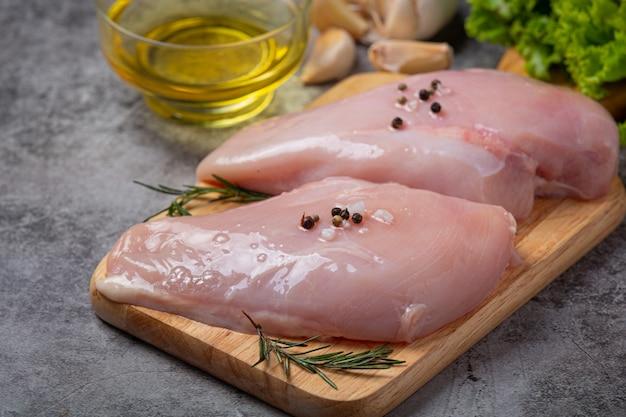 Peito de frango cru na superfície escura.