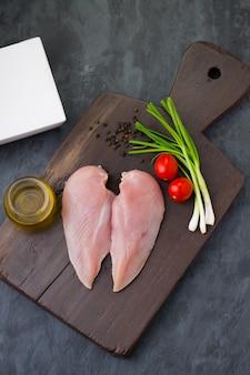 Peito de frango cru sem pele fresco disposto em uma placa de madeira