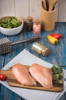 Peito de frango de alto ângulo na placa de madeira com salsa
