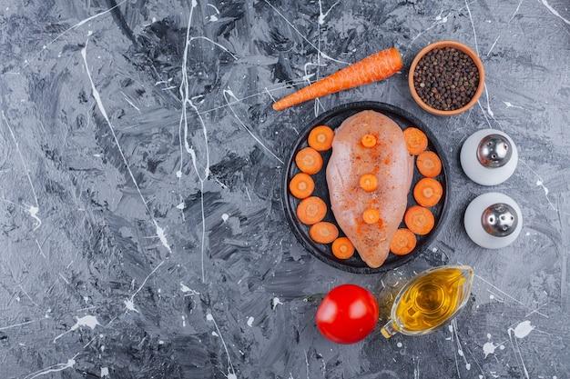 Peito de frango e cenouras fatiadas em um prato ao lado de sal, óleo, especiarias, cenoura e tomate na superfície azul