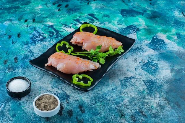 Peito de frango e legumes em uma travessa ao lado de tigelas de temperos, no fundo azul.