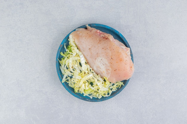Peito de frango e verduras no prato de madeira, na superfície branca