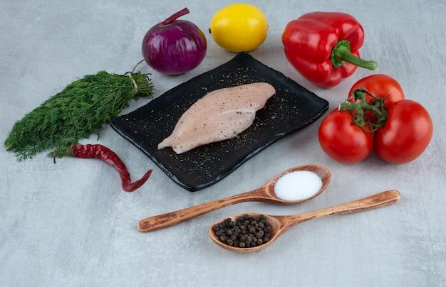 Peito de frango, especiarias e vários vegetais na superfície cinza.