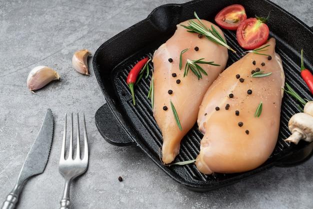 Peito de frango fresco e temperos na frigideira