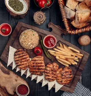 Peito de frango frito com batatas fritas e vista superior de arroz