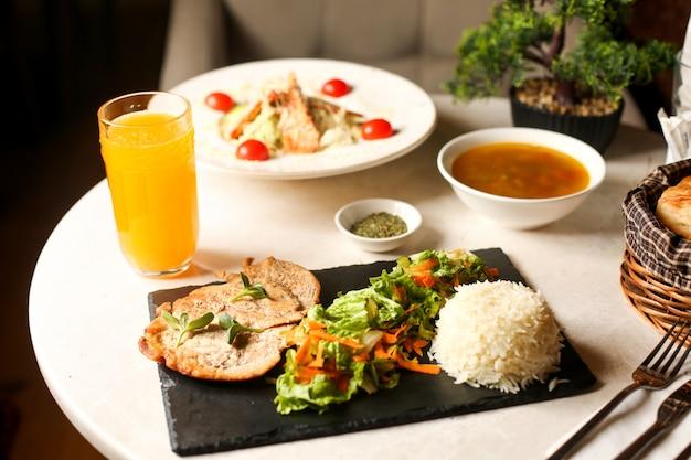 Peito de frango frito servido com salada de alface e arroz