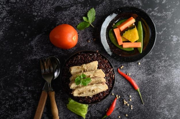 Peito de frango grelhado coberto com pimenta em bagas maduras de arroz roxo.