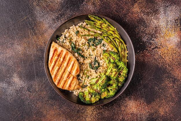 Peito de frango grelhado com arroz integral, espinafre, brócolis, aspargos, conceito de dieta, alimentação saudável.