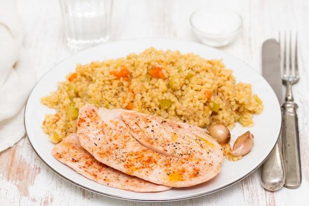 Peito de frango grelhado com cuscuz no prato branco