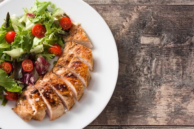 Peito de frango grelhado com legumes em um prato na mesa de madeira. vista do topo.