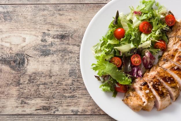 Peito de frango grelhado com legumes em um prato na mesa de madeira. vista superior.