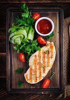 Peito de frango grelhado com legumes frescos na tábua de madeira. jantar saudável. vista superior, espaço de cópia, sobrecarga
