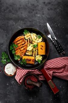 Peito de frango grelhado com milho e abobrinha em uma vista superior da assadeira grelhada. prato de verão com frango grelhado e legumes.