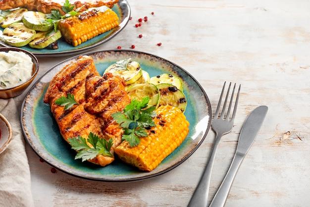 Peito de frango grelhado com milho e abobrinha em uma vista superior de placa azul. prato de verão com frango grelhado e legumes.