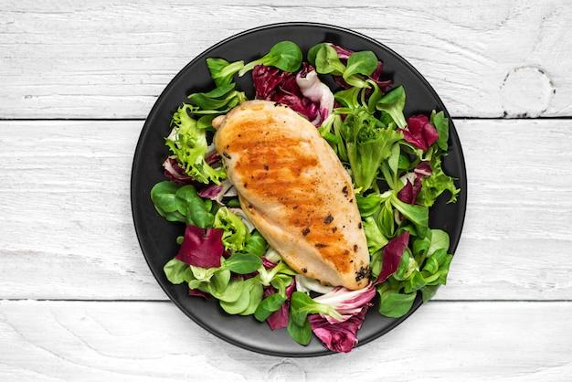 Peito de frango grelhado com salada mista em um prato preto