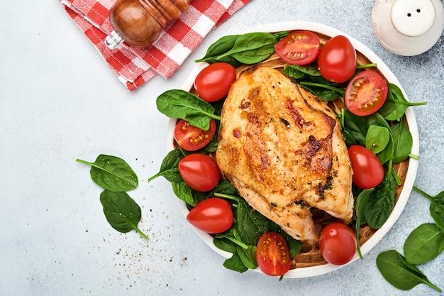 Peito de frango grelhado com salada verde de espinafre, pimenta e tomate cereja em um prato de cerâmica no fundo da mesa branca. alimentação saudável, dieta cetogênica, conceito de almoço. vista superior e espaço da cópia.
