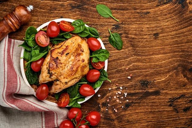 Peito de frango grelhado com salada verde de espinafre, pimenta e tomate cereja em uma placa de cerâmica em um fundo de mesa de madeira velha. vista do topo.