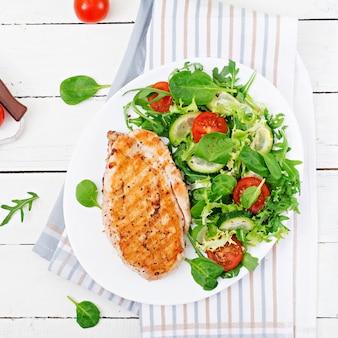 Peito de frango grelhado e salada de legumes frescos - folhas de tomate, pepino e alface. salada de galinha. comida saudável. postura plana.