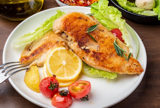 Peito de frango grelhado e salada de legumes no prato