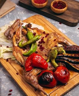 Peito de frango grelhado em diferentes variações com tomate cereja, pimentão verde em uma placa de madeira.