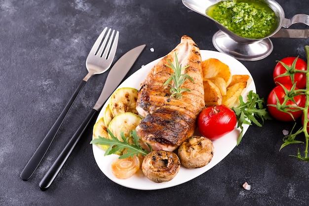Peito de frango grelhado em um prato com tomate, cogumelos e molho verde em uma pedra, lay plana