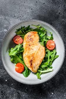 Peito de frango grelhado. filé de frango e salada de legumes frescos com folhas de tomate e rúcula. fundo preto. vista do topo