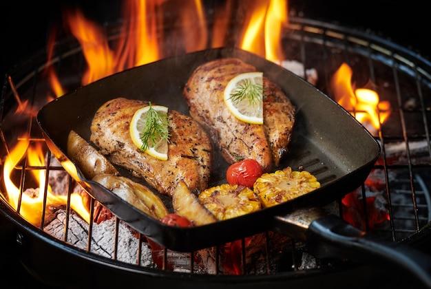 Peito de frango grelhado na grelha em chamas com tomates vegetais grelhados, ervas, limão, alecrim. menu de almoço saudável.