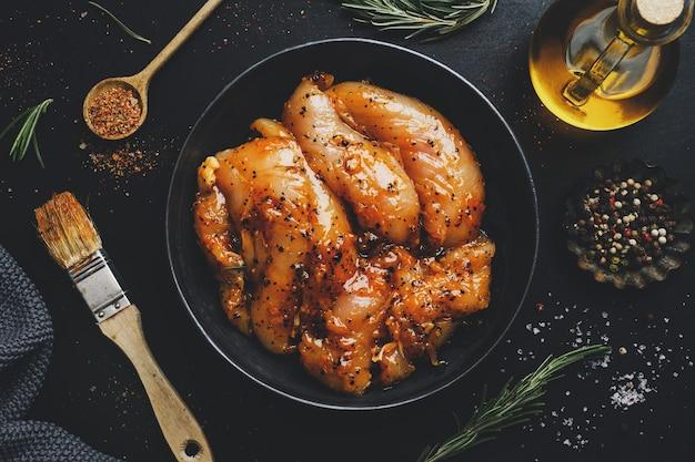 Peito de frango marinado cru na superfície escura com especiarias prontas para cozinhar