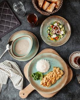 Peito de frango picado, preparado com molho e servido com salada de arroz e sopa