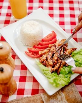 Peito de frango picado, servido com tomate, alface e arroz
