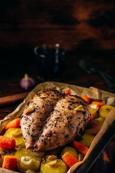 Peito de frango temperado assado no forno com legumes na assadeira