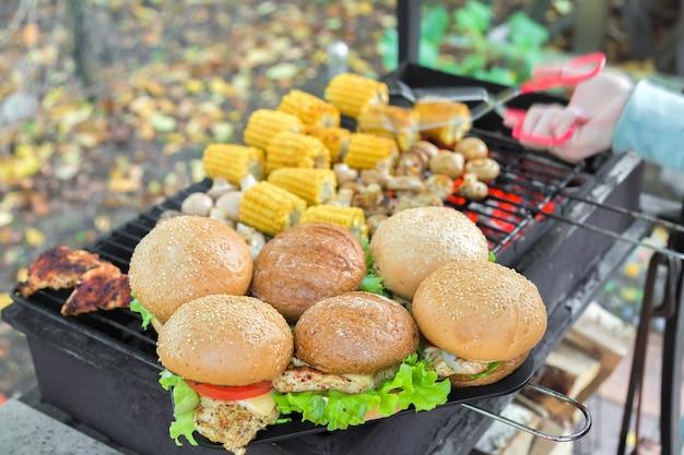 Peito de hambúrgueres de churrasco com legumes na churrasqueira a carvão quente com a mão no fundo
