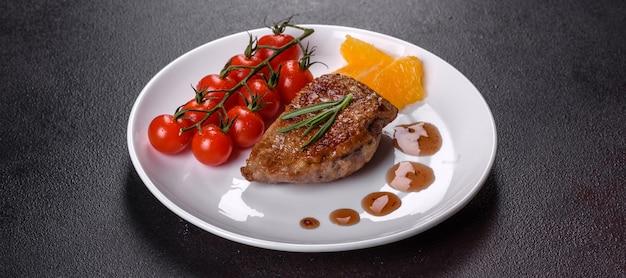 Peito de pato assado com ervas e especiarias em um fundo escuro de concreto. carne frita pronta para comer
