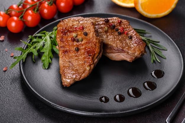 Peito de pato assado com ervas e especiarias em uma superfície de concreto escura. carne frita pronta para comer