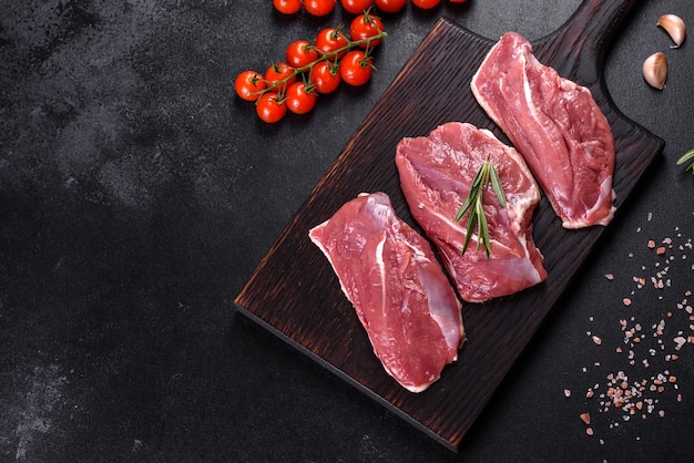 Peito de pato cru com ervas e especiarias em uma mesa escura. carne crua preparada para assar