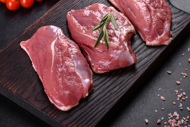 Peito de pato cru com ervas e especiarias em uma superfície de concreto escura. carne crua preparada para assar Foto Premium
