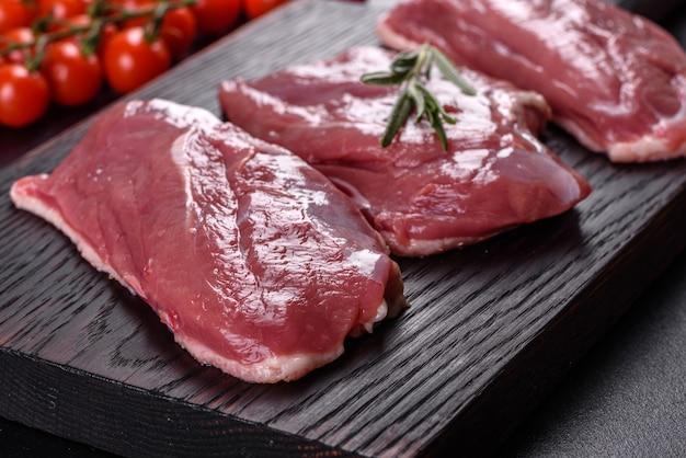 Peito de pato cru com ervas e especiarias em uma superfície de concreto escura. carne crua preparada para assar