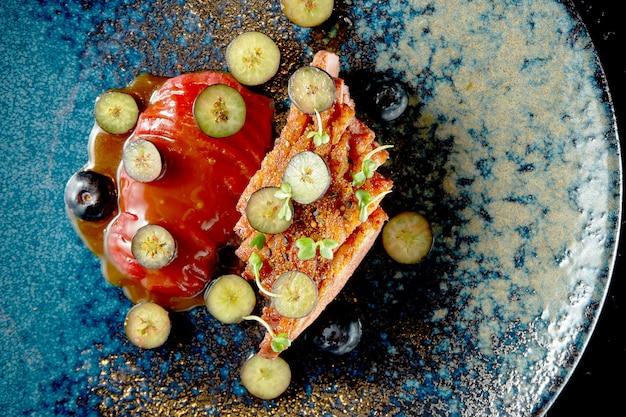 Peito de pato frito com confit de frutas e mirtilos. entrega de alimentos. isolado no preto