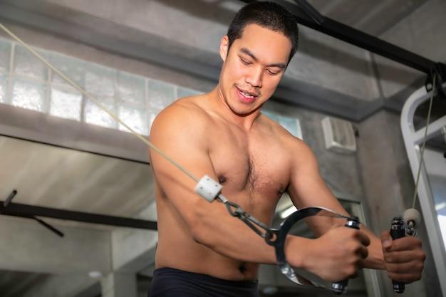 Peito de treino atlético homem musculoso bonito asiático com cabo no ginásio de fitness.