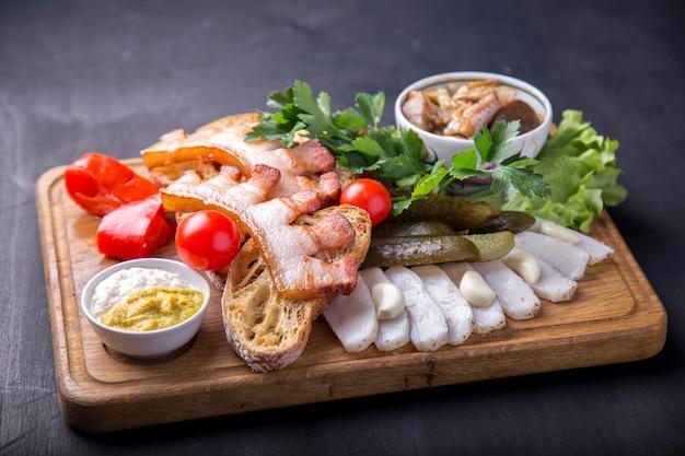 Peito frito com pedaços de pão frito, banha de porco cortada, tomates frescos e cogumelos marinados. aperitivo saboroso na placa de madeira