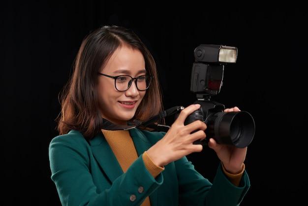 Peito para cima retrato de uma fotógrafa asiática asiática tirando uma foto