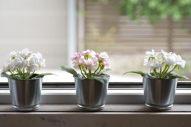 Peitoril da janela com três vasos de flores em um fundo desfocado