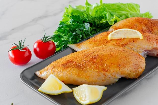 Peitos de frango crus com salsa e tomate pronto para cozinhar. alimentos dietéticos.