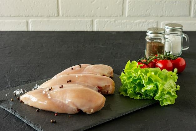 Peitos de frango crus com salsa e tomate pronto para cozinhar.
