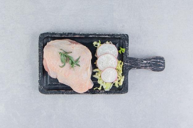 Peitos de frango crus e temperos no quadro, na superfície branca